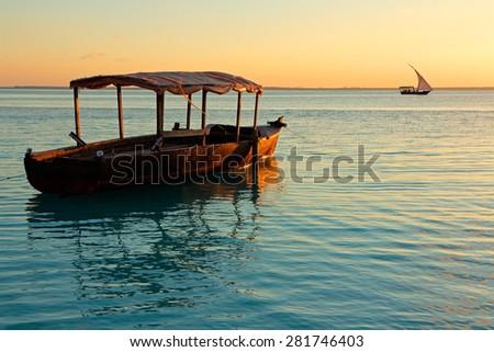 Wooden boat on water at sunset, Zanzibar island - stock photo