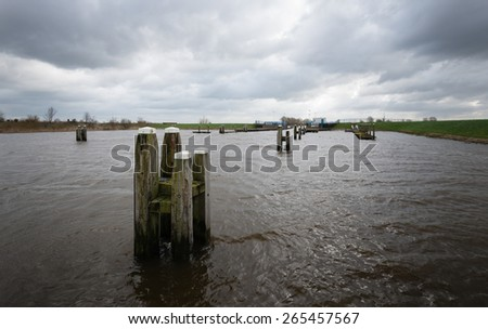 Wooden bollards in a rough river during stormy weather with ominous clouds on the dark sky. - stock photo
