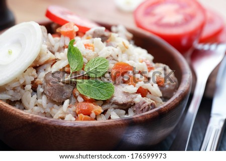 Wooden bowl full of freshness pilaw near fork and knife - stock photo