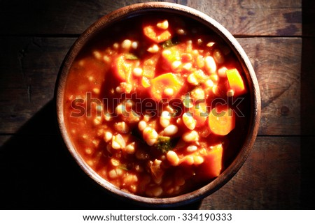 Wooden bowl full of stewed beans on old wooden background - stock photo