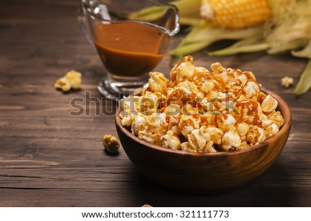 Wooden bowl full of sweet caramel popcorn with caramel sauce and corncobs over rustic table. Vintage style. Selective focus - stock photo