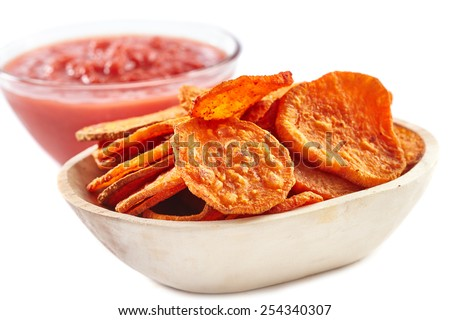 Wooden bowl full with homemade sweet potatoes chips and tomatoes sauce in background, isolated on white - stock photo
