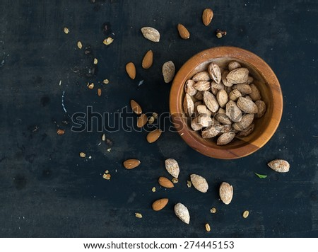 Wooden bowl of salty almond nuts in nutshell grunge dark backdrop. Top view, copy space - stock photo