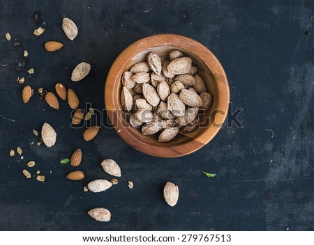 Wooden bowl of salty almond nuts in nutshell grunge dark backdrop, top view, copy space - stock photo