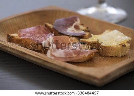 Wooden bowl on a table with Italian bruscetta with salami, meat and cheese - stock photo