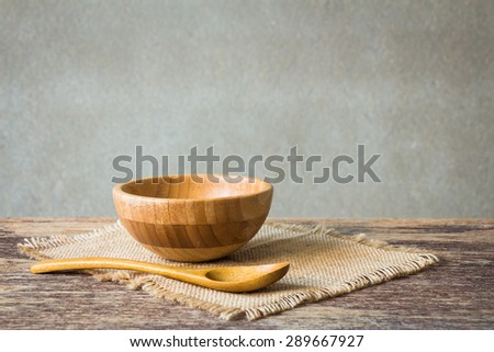 wooden bowl on wooden table over grunge background, rustic style  - stock photo