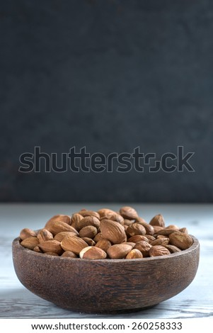 Wooden bowl with almonds on the table,selective focus and blank space  - stock photo