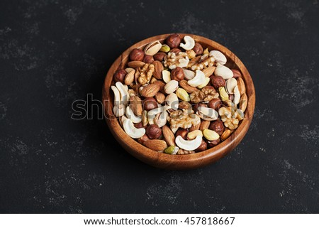 Wooden bowl with mixed nuts on black table from above. Healthy food and snack. Walnut, pistachios, almonds, hazelnuts and cashews. - stock photo