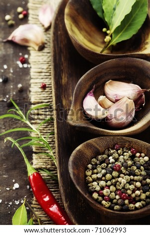 wooden bowls with fresh herbs and spices ( garlic, pepper, bay leaves, salt) - stock photo