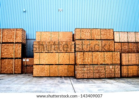 Wooden boxes for transportation and a blue cladding in a warehouse - stock photo