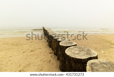 Wooden breakwater, beach and sea in the fog - stock photo