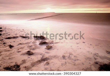 Wooden breakwater in wavy Baltic Sea. Romantic atmosphere at smooth wavy sea. Pink horizon with first hot sun rays. - stock photo