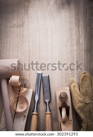 Wooden bricks hammer curled up scobs planer firmer chisels leather gloves on wood background construction concept. - stock photo