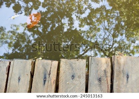 Wooden bridge and trees reflected in water view from above - stock photo