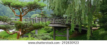 Wooden Bridge crossing over a river to a Japanese Garden - stock photo