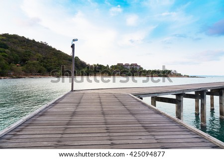 Wooden bridge leading to the sea with mountain background, natural landscape - stock photo