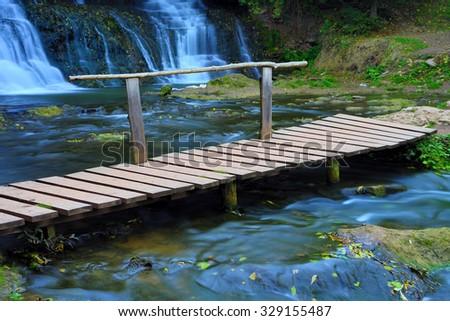 Wooden bridge over river stream - stock photo