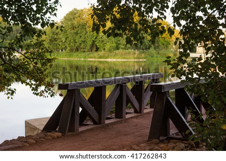 Wooden bridge surrounded by green trees in a park near lake at summer time - stock photo