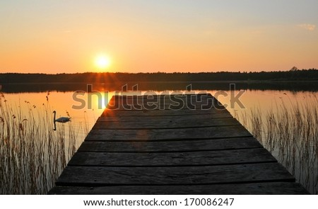 Wooden bridge to the lake under the sunset - stock photo