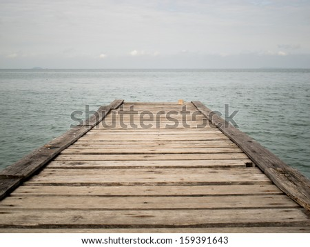 Wooden Bridge to the sea,blue sea and clouded sky - stock photo