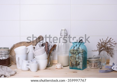 Wooden buffet counter with kitchenware, sweets, milk bottle and milled coffee. White background. - stock photo