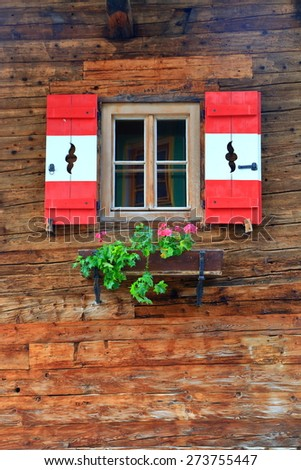 Wooden building wall with traditional window decorated with flowers, Tirol, Austria - stock photo