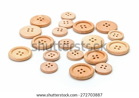 Wooden buttons of various sizes on white surface - stock photo