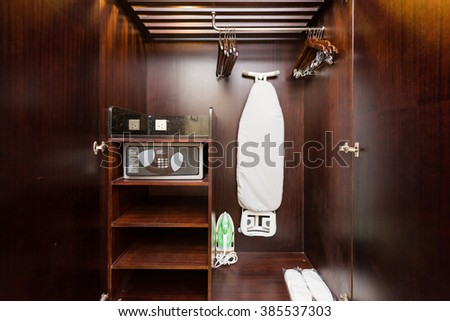 Wooden cabinet containing ironing board and security safe. - stock photo