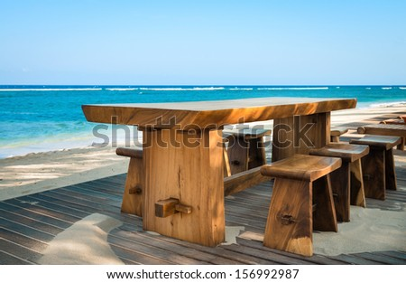 Wooden cafe table and chairs on a tropical beach with blue sea on background - stock photo