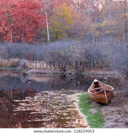 Wooden canoe beside a pond. - stock photo