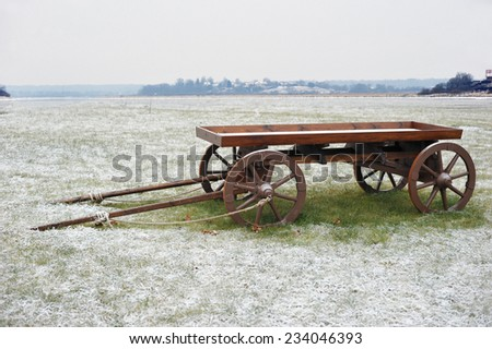 wooden cart in snowy field - stock photo