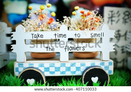 """Wooden cart with message """"Take Time to Smell The Flowers"""" - stock photo"""