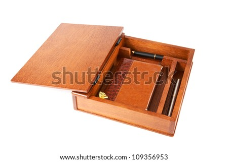 Wooden casket with  notebook and pens on a white background - stock photo