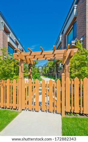 Wooden cedar yellow fence and gates to the townhouses  complex. Nice and comfortable neighborhood. Townhouses in the suburbs of the North America. Canada. - stock photo