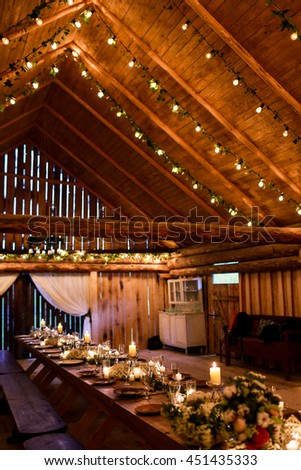 Wooden ceiling decorated with light bulbs which hang over the dinner table - stock photo