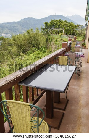 wooden chair and table outside with mountain view - stock photo