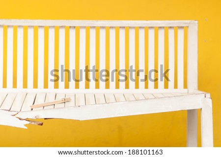 Wooden chair broken with yellow walls in the building - stock photo