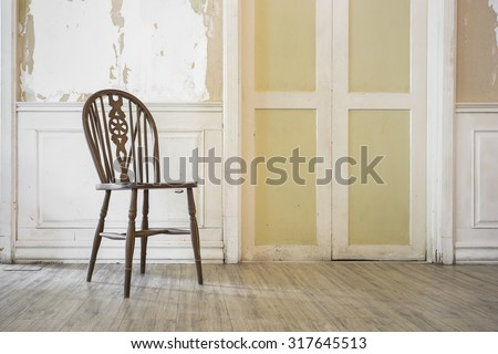 wooden chair in vintage old room with peeled off paint and grunge wallpaper - stock photo