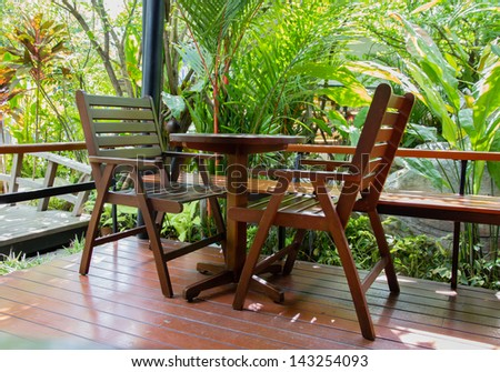 Wooden chair on a balcony in the garden. - stock photo