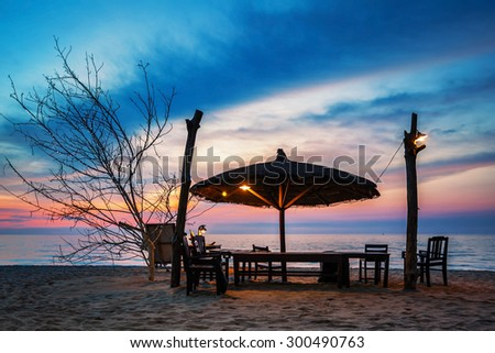 Wooden chairs and umbrella on white beach in sunset time at Phu Quoc island in Vietnam - stock photo