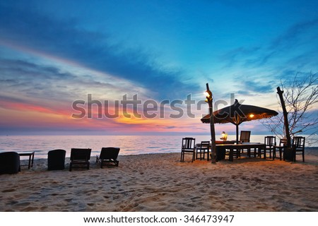 Wooden chairs and umbrellas on white beach in sunset time at Phu Quoc island in Vietnam - stock photo
