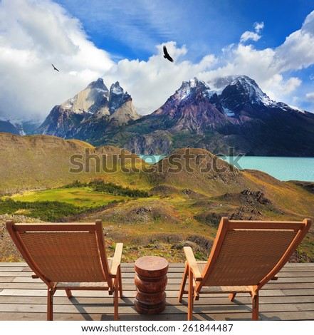 Wooden chairs in the park Torres del Paine. On the horizon is visible snow-covered rocky mountain. Pleasant holiday in Chile - stock photo