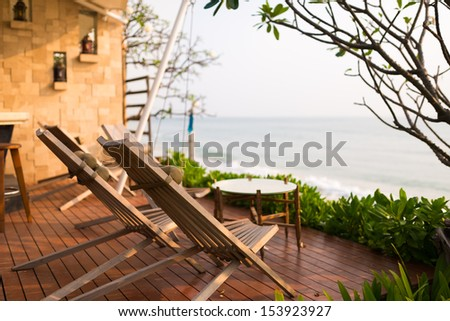 Wooden chairs on balcony of hotel by the beach - stock photo