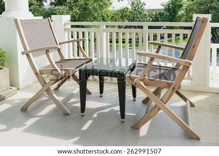 wooden chairs on modern balcony overlooking a garden - stock photo