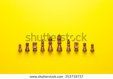 Wooden chess figurines organized in a row over yellow background - stock photo
