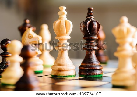 wooden chess pieces on gray background - stock photo