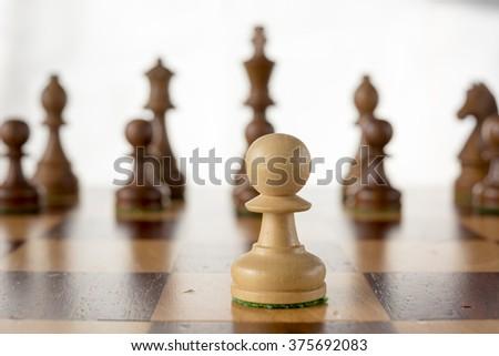 wooden chess set, white pawn opposit black enemy team  on board - stock photo