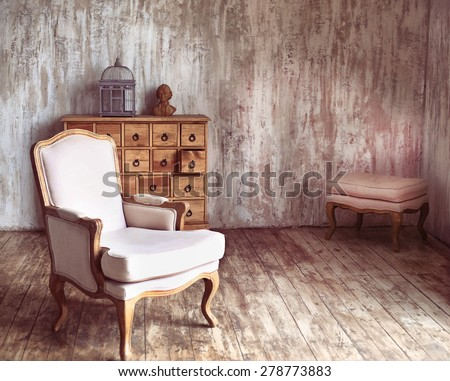 wooden chest of drawers in shabby styled room with bird cage and Mozart bust - stock photo