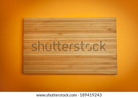 Wooden Chopping Board with orange background - stock photo
