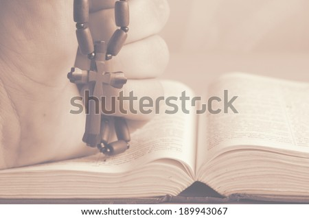 wooden Christian cross in his hand on the Bible. art toning. - stock photo